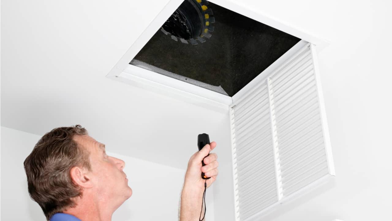 Man checking an air duct