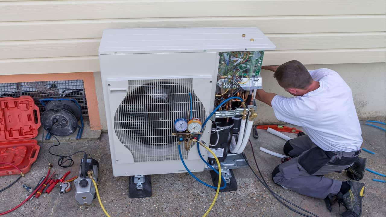 Man repairs a heat pump