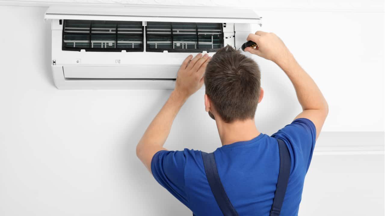 Technician fixing an AC unit