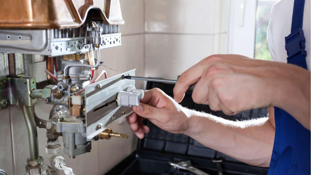 Technician repairs a water heater